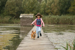 Girl and dog running Royalty Free Stock Images
