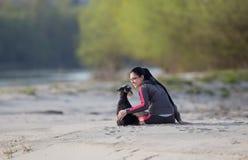 Girl with dog on sandy coast Stock Photography