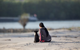 Girl with dog on sandy coast Stock Images