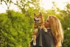Girl and dog Shiba Inu embrace. Stock Photography