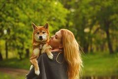 Girl and dog Shiba Inu hug. Royalty Free Stock Photos