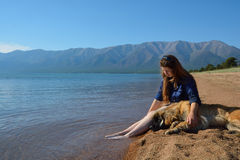 Girl with a dog on the shore of Lake Baikal Royalty Free Stock Photography