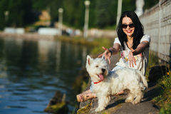 Girl with a dog on the shore Stock Photos