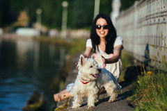 Girl with a dog on the shore Stock Photography