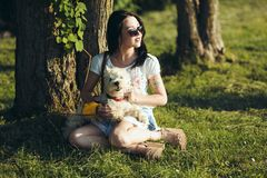 The girl with dog sit on a grass Royalty Free Stock Images