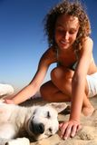 Girl with dog sits on sand Royalty Free Stock Images