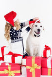 Girl and dog are sitting with christmas gifts Stock Image