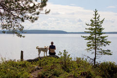 Girl with a dog sitting on a rock at the lake Stock Photos