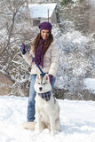Girl with dog in snowy forest Stock Photography