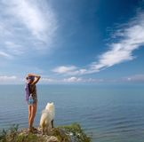 Girl and dog standing on precipice. Girl with bottle and samoyed dog standing on precipice above sea Royalty Free Stock Photo