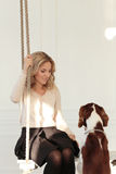 Girl with a dog. On the swing stock image