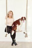 Girl with a dog. On the swing royalty free stock image