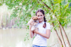 Girl with a dog. Teenage girl with long braids standing there smiling with a dog on the banks of the river stock photography