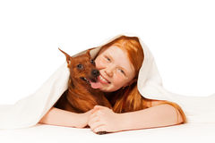 Girl with dog under the blanket Stock Photo