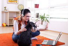 Girl with dog using video call on laptop. Girl with dog sitting on the floor in the room and talking on video call on laptop stock image