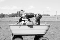 Girl and dog in wagon
