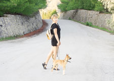 Girl with dog walking on  road Stock Photography