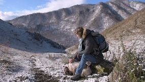 Girl with a dog in the mountains. The girl with the dog walks in the mountains. It is snowing, the sun is shining stock footage
