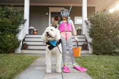 Girl With Dog Wearing Halloween Costumes For Trick Or Treating stock photography