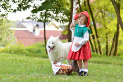 Girl with a dog wearing red hood Stock Photos