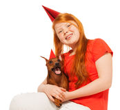 Girl and dog wears party birthday caps Royalty Free Stock Image