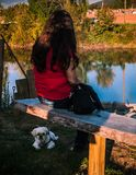 Girl And Dog. Girl or Women`s back to the camera overlooking a river with her dog sitting beneath her on a bench Royalty Free Stock Images