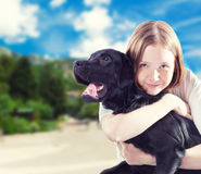 Girl with a dog. Young woman hugs her labrador dog outdoors Royalty Free Stock Photography