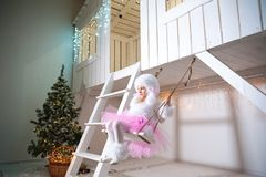 A girl in a doggie dress on a swing at the facade of a white wooden house decorated for Christmas and New Year. A girl in a doggie dress swings on a swing at the royalty free stock image