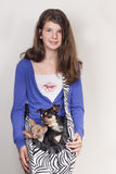 Girl with dogs. Smiling young girl with a bag with two dogs inside Stock Image