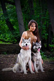 Girl with dogs at forest Royalty Free Stock Photos