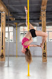 Girl doing acrobatics on pole Royalty Free Stock Photos