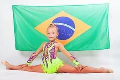 Girl doing artistic gymnastics element, split. Brazilian flag Royalty Free Stock Photos