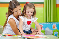 Girl doing arts and crafts. With mother in nursery room Stock Photography