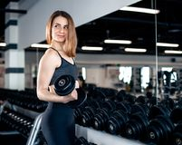 Girl doing bicep exercise with dumbbells stock photo
