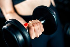 Girl doing bicep exercise with dumbbells royalty free stock photo