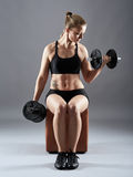 Girl doing biceps curl with dumbbells Stock Images