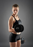 Girl doing biceps curl with dumbbells Royalty Free Stock Photo