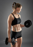 Girl doing biceps curl with dumbbells Stock Photos