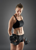Girl doing biceps curl with dumbbells Royalty Free Stock Image