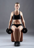 Girl doing biceps curl with dumbbells Royalty Free Stock Photography