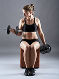 Girl doing biceps curl with dumbbells Stock Image