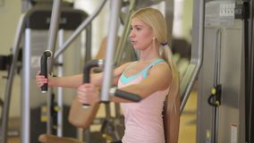 Girl doing butterfly exercises on a pec deck stock footage