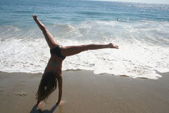 Girl Doing Cartwheel on the Beach. Young girl doing a cartwheel on the beach as the waves roll in Stock Photography