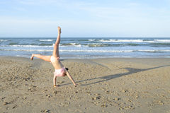 Girl doing cartwheel on the beach Stock Images