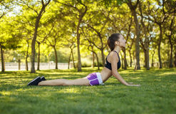 Girl doing cobra pose on the grass royalty free stock image