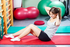 Girl doing crunches on gym mat Stock Photo