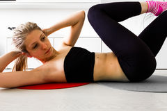 Girl doing crunches in her living room Royalty Free Stock Images