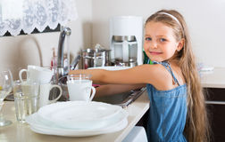 Girl doing dishes at kitchen. Independent little girl doing dishes at kitchen Royalty Free Stock Photo