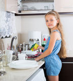 Girl doing dishes at kitchen Stock Photos