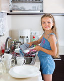 Girl doing dishes at kitchen Stock Image